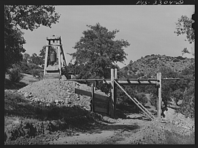 Kern County, California. Tungsten Chief Mine. One of the shafts. Ore is loaded into hand cars and pushed out onto an overhead trestle where it is dumped into trucks for transport to the mill