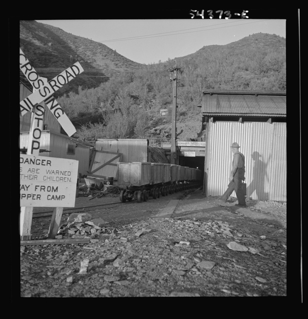 Kingman (vicinity), Arizona. A miner going toward a train of mine cars at the entrance of the Boriana mining company. These cars carry tungsten ore to a concentrating plant in the same area. The mine is about forty miles from Kingman
