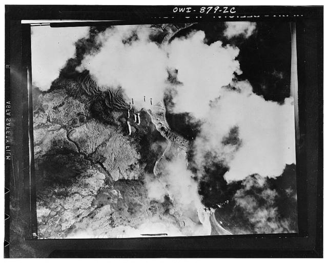 Kiska, Aleutian Islands. Bombs dropping in train from a United States Army Air Force plane on a Jap objective. Our flyers in Alaska relentlessly pursue their assignment to blast the Japs from their Aleutian holdings. This is an unusually clear shot, for the area thereabouts is fog-bound a good deal of the time