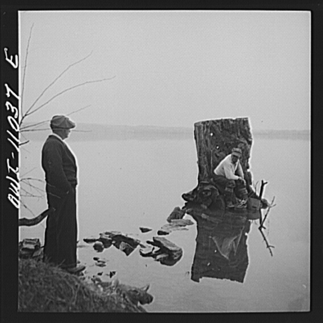 Lancaster County, Pennsylvania. Fishing for salmon on the Susquehanna River at 6 p.m. This man is a state supervisor of highways. In his time off late in the afternoon he fishes with a bottle of hard cider beside him