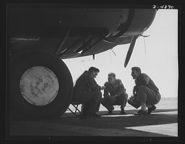 Langley Field, Virginia. YB-17 bombardment squadron. A staff sergeant and two corporals of a bombardment squadron stationed at Langley Field, Virginia thrash out a technical problem that arose during the servicing of the mighty YB-17 bomber that towers above them