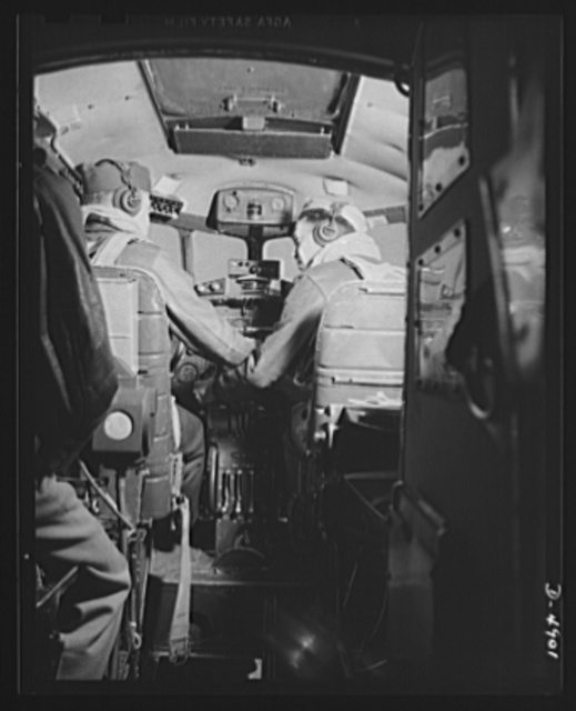"Langley Field, Virginia. YB-17 bombardment squadron. Important business is transcated in the ""office"" of a mighty YB-17 bomber. The pilot captain and co-pilot lieutenant confer before taking off on a military mission from Langley Field, Virginia"