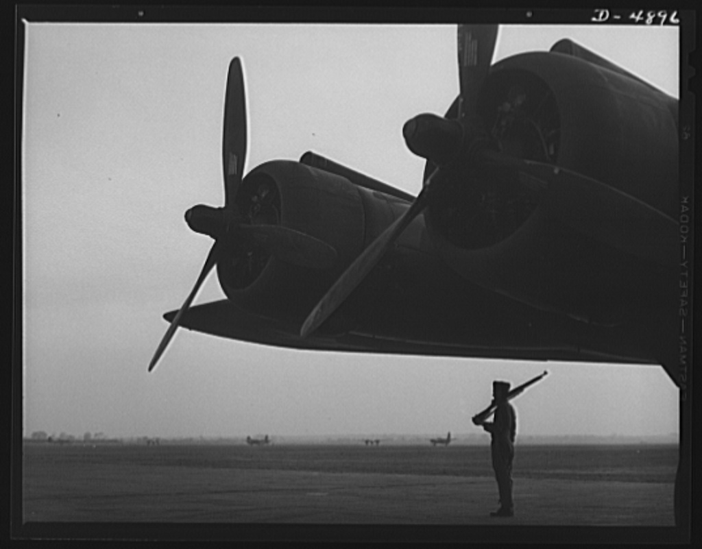 Langley Field, Virginia. YB-17 bombardment squadron. Silhouetted against the dawn, a soldier of a bombardment squadron at Langley Field, Virginia keeps faithful watch over a giant YB-17 bomber.