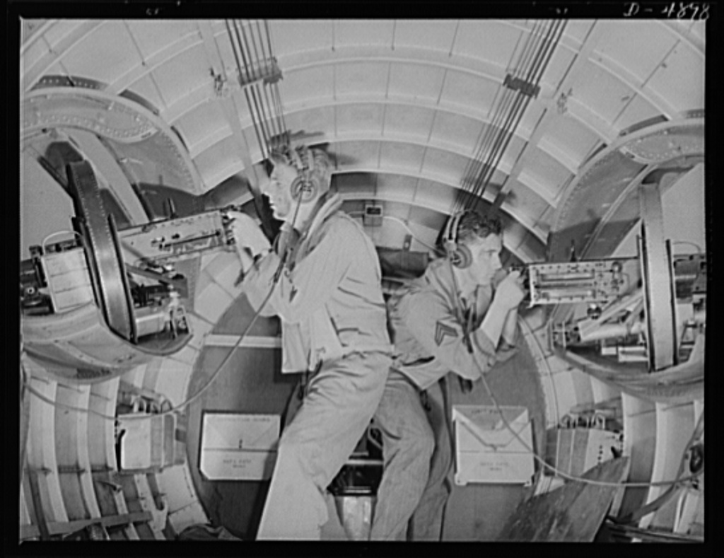Langley Field, Virginia. YB-17 bombardment squadron. Two good reasons why our air forces will be unpopular with the Axis. These corporals operating side machine guns in a mighty YB-17 bomber have developed into fast, accurate gunners