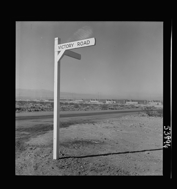 """Las Vegas, Nevada. A crossroad sign reading """"Victory Road,"""" with buildings, storage silos and transmission lines of the Basic Magnesium Incorporated plant in the background"""
