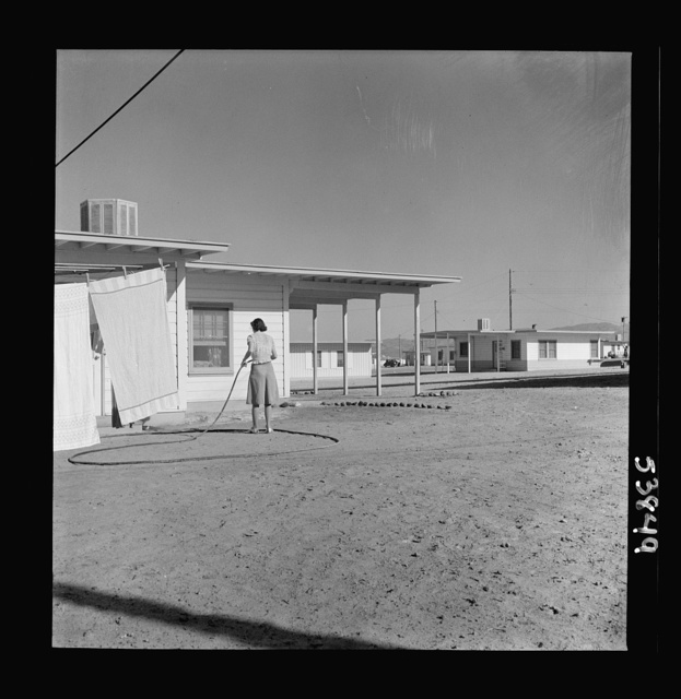 Las Vegas, Nevada. A worker's wife watering a newly planted lawn around one of the thousand demountable houses built adjacent to the Basic Magnesium Incorporated plant in the southern Nevada desert