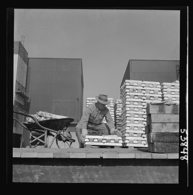 Las Vegas, Nevada. Enormous asbestos mittens are worn by the worker handling the hot magnesium ingots produced at the Basic Magnesium Incorporated plant in the southern Nevada desert