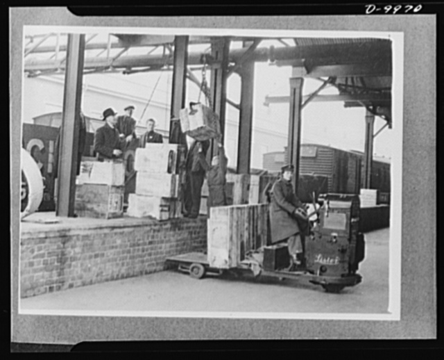 Lend-Lease to Britain. Cases of American spare parts arriving at an English ordnance center as part of a lend-lease shipment from the United States are moved to the stores for unloading. English girls, driving trucks, help with the task