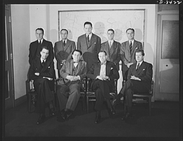 Leon Henderson and staff. Deputy administrators of the Office of Price Administration (OPA) with Leon Henderson, Administrator, in Washington, D.C. just prior to Mr. Henderson's retirement from office. Seated, left to right, J.K. Galbraith, Mr. Henderson, John E. Hamm, David Ginsburg. Standing, left to right, Dexter M. Keezer, Paul M. O'Leary, Paul A. Porter, Edward N. Hay, Robert W. Horton