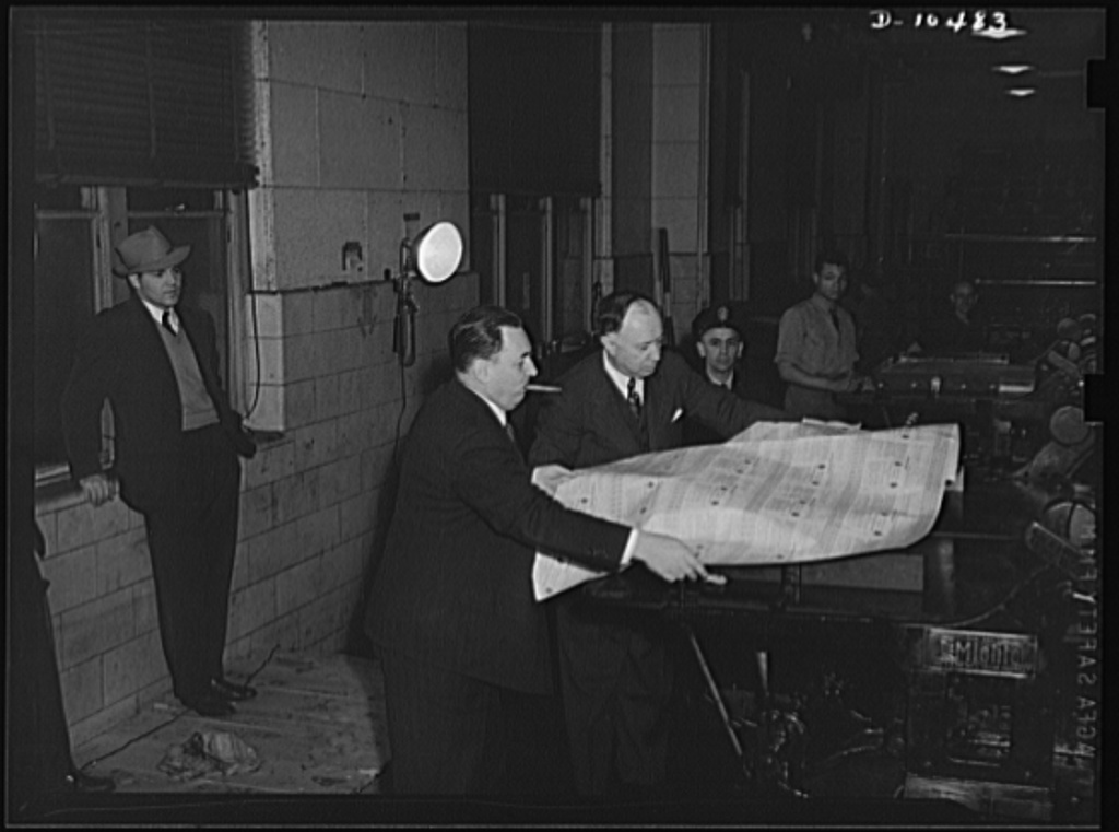 Leon Henderson gets the first proof of war ration book no. 1 from a press at the Government Printing Office (GPO)---acting public