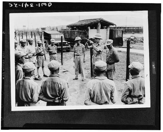 Lieutenant Carl Arnold, instructor, giving Chinese troopers their first lesson in the use of drumsticks