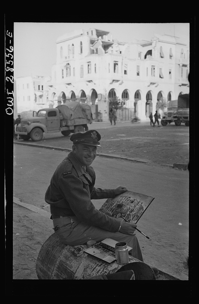 Lieutenant Milton Marx of New York City, attached to the Public Relations Office of the United States Army Ninth Air Force, does some painting in the streets of Tripoli. In civilian life Marx is a commercial artist