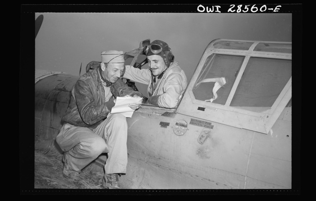 """Lieutenant Robert """"Rocky"""" Byrnes (in the plane), twenty-six, Saint Louis, Missouri, flying with the Sixty-fourth Squadron of the Fifty-seventy Fighter Group is seen here as he landed after destroying three ME-109's. The Fifty-seventh United States Fighter Group of the Ninth Air Force destroyed seventy-four enemy planes in the same action. Lieutenant Byrnes now has four enemy fighter planes to his credit. He was a pro baseball player with Cincy farm system before the war. Captain Carl A. Nelson, Los Angeles, California, intelligence agen for Sixty-fourth, getting details of Byrnes' part in action"""