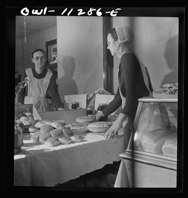 Lititz, Pennsylvania. Mennonite woman arranging baked goods at the farmers' market
