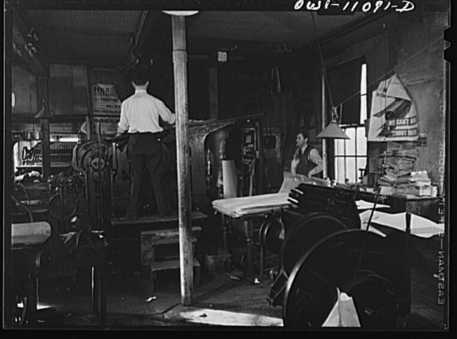 Lititz, Pennsylvania. Press room of the Lititz Record-express. Publisher Young waits for a bunch of papers to come off the press so that he can take them into the cutting and folding machine