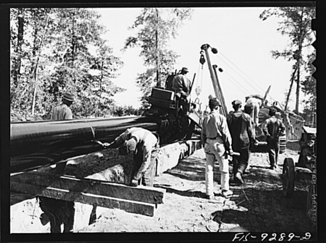 Little Rock, Arkansas. to Missouri-Arkansas state line. War emergency pipeline from Longview, Texas to Norris City, Illinois. Priming pipe with hot asphalt paint. Crew follows machine and touches up by hand space where pipe is welded together