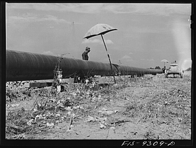 Little Rock, Arkansas to Missouri-Arkansas state line. War emergency pipeline from Longview, Texas to Norris City, Illinois. Pipeline cutting through cotton field