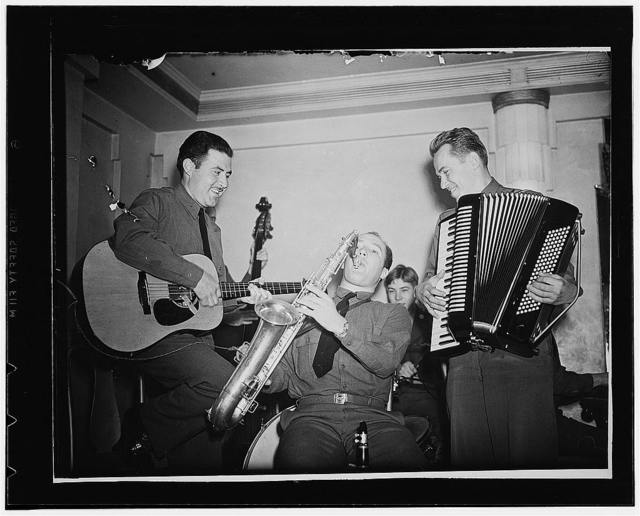 London, England. Three members of the band at the Red Cross Washington club in London. Left to right: Private Jesse Cosrales, of Los Angeles; Private Donald Beverly, of Elgin, Illinois, and Sergeant Pete Balutis, of Kewanee, Illinois
