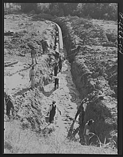 Longview, Texas to Arkansas state line. War emergency pipeline from Longview, Texas to Norris City, Illinois. Laborers removing mud and water from the drag hole