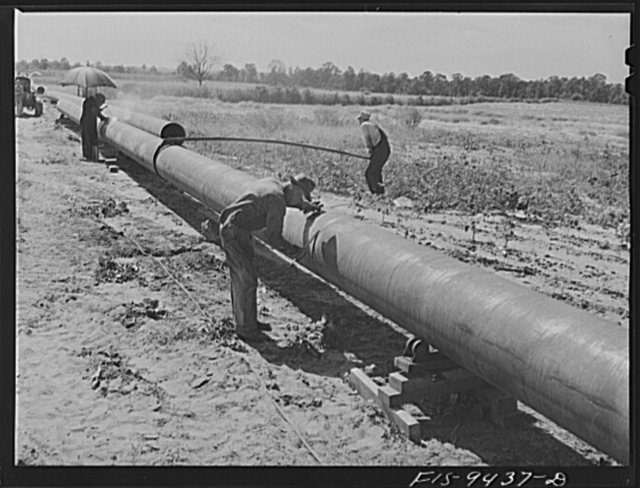 Longview, Texas to Arkansas state line. War emergency pipeline from Longview, Texas to Norris City, Illinois. Welders on the firing line. Assistant slowly rotates pipe while welders work