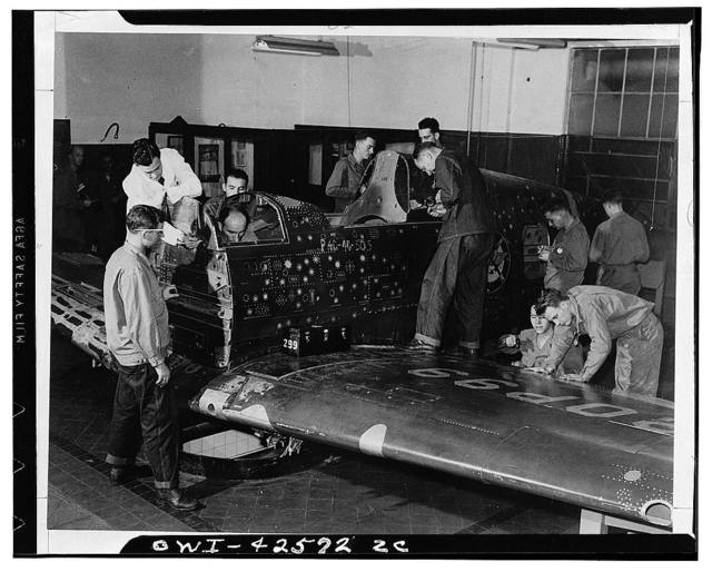"""Los Angeles, California. """"Flying Patch,"""" a Currtiss """"Warhawk"""" fighter plane complete except for engine and tail assembly, with simulated bullet holes and patches. It is used at the sheet metal mechanics school operated by the Anderson organization for the United States Army air force technical training command. The soldier trainees are shown punching holes, measuring for patch sizes, drilling, and riveting"""
