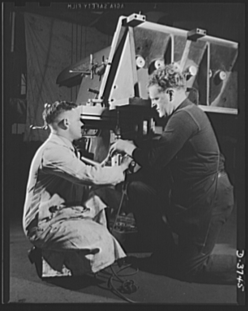 Machine tool experts set up a fixture to be used in drilling tank engine cylinder bores. The no. 4 Cincinnati horizontal mill which will do the work is one of many fine machines in a big automobile factory now being converted to tank production. Ford Lincoln plant, Michigan