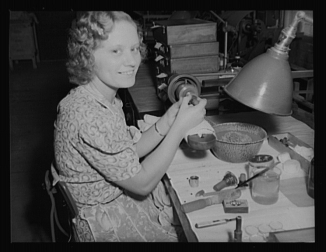 Making eyes for the army. Polishing lenses by hand in the optical department of an Army arsenal, where thousands of sights for guns are being turned out