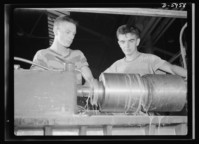 Manpower. Americans all. Operating a low-swing engine lathe, Joe Zorich (left) and Chuck Doe, both nineteen, are typical of the younger workers in this huge Midwest medium-tank factory. Both are first-generation Americans--Joe's parents came from Croatia and Chuck's from Germany--and both are just about as American as any nineteen-year-old who can count his American-born ancestors on both hands. Machining parts for the tanks American soldiers will use to defeat the Axis, they're marking time till they can be on the front lines themselves, using these very tanks to make a first-hand stab at Hitler's hordes. Pressed Steel Can Company, Chicago, Illinois
