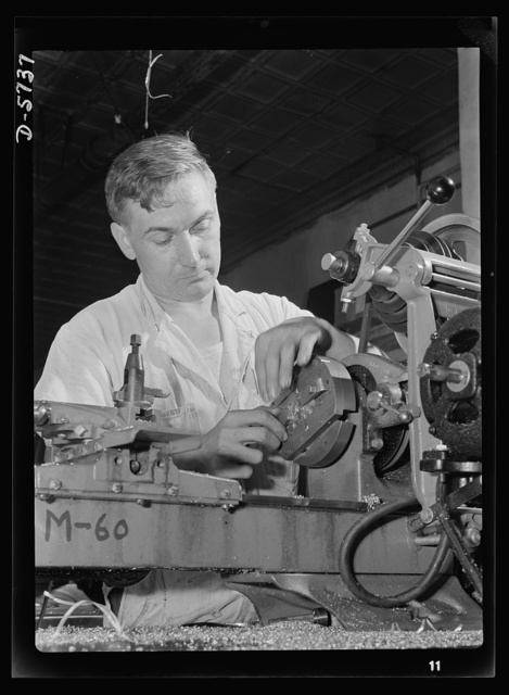 Manpower. Handicapped workers. Joseph Witte, twenty-eight years old, is one of Uncle Sam's disabled war workers. With both legs afflicted by infantile paralysis, he's nevertheless an expert lathe operator and assistant foreman in a Baltimore factory. He's shown here turning the inside radius of spacers, which are part of an airplane motor's supercharger. White Engineering Company, Baltimore, Maryland