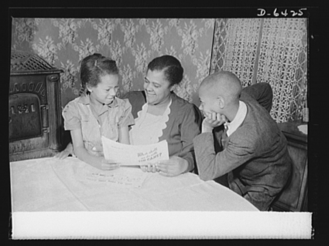 "Manpower, junior size. ""Helping Uncle Sam is the best possible work for you,"" Mrs. Bertha Traynham, an evangelist, tells her grandchildren, junior commandos in Roanoke, Virginia. The children have brought her leaflets explaining the necessity of the scrap collection drive"