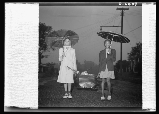 "Manpower, junior size. ""Neither rain nor snow...nor gloom of night...stays these couriers from the completion of their appointed rounds."" Junior commandos of Roanoke, Virginia, these two young girls are making their weekly rounds of all available scrap in their neighborhood, despite unfavorable weather"