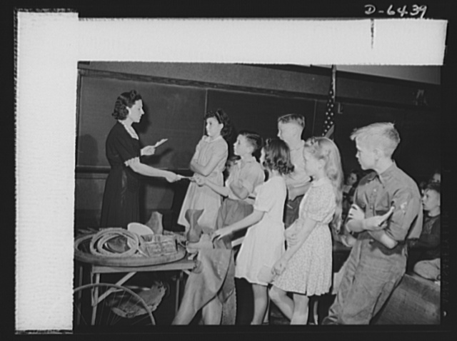 Manpower, junior size. Notes from parents giving permission to their sons and daughters to join the Roanoke, Virginia junior army are received by teacher Doris Jordan. Now these newly appointed junior commandos are ready to collect scrap for victory