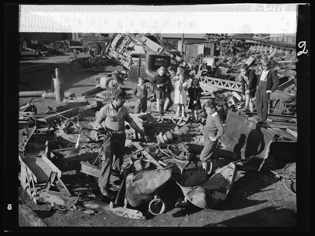 Manpower, junior size. Proud young fighters in Uncle Sam's junior army visit a scrap yard in Roanoke, Virginia to see for themselves what happens to the scrap they collect for our war industries. One of the workers explains to the children how the acetylene torch he holds cuts heavy metal into the shapes required for melting by the steel mills