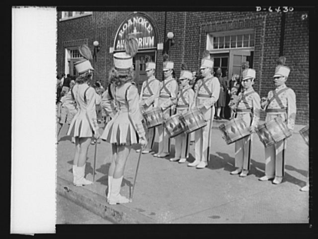 """Manpower, junior size. The spirit of '42. The Jefferson High School drum and bugle corps in Roanoke, Virginia started the junior commando rally with a fanfare and a drum roll. Outside of the auditorium, the """"military band"""" prepared to enter the hall where Roanoke school children awaited the opening of the rally that was to number them as part of America's junior army to collect scrap for our armed forces"""