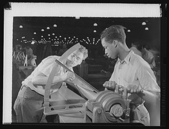 Manpower. Negro aircraft propeller workers. Americans of various racial groups contribute to the war effort. One worker adjusts the blade in a vise while another reads the angle in a large Eastern plant producing propellers for military aircraft. Curtiss-Wright Propeller Division. Caldwell, New Jersey