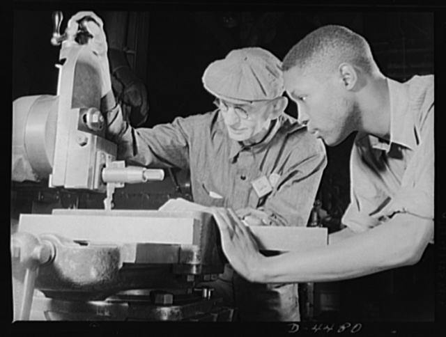 Manpower. Negro navy yard workers. From the aged and the youthful, from the white and the Negro come the skills which will make America impregnable. A veteran employee in an Eastern navy yard instructs an apprentice machinist in the operation of an important machine
