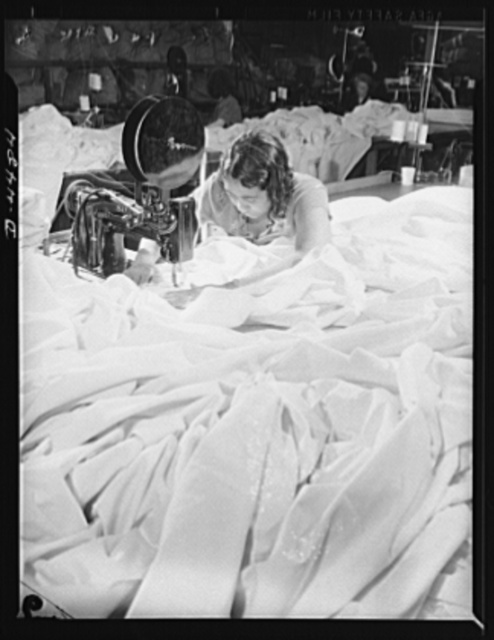 Manpower. Negro navy yard workers. In a sea of silk, this woman worker is making parachutes for America's paratroopers. She is one of many Negro employees in the aircraft factory of an Eastern navy yard