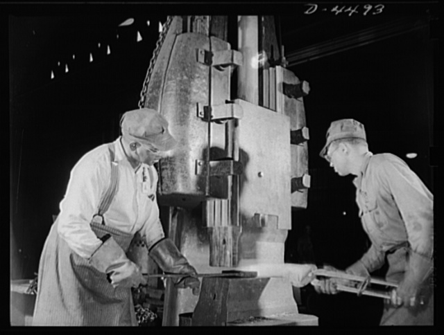 Manpower. Negro navy yard workers. The brawn of the village smith is dwarfed in this modern blacksmith shop where a powerful drop hammer fashions a red hot metal slab for ship construction in an Eastern navy yard