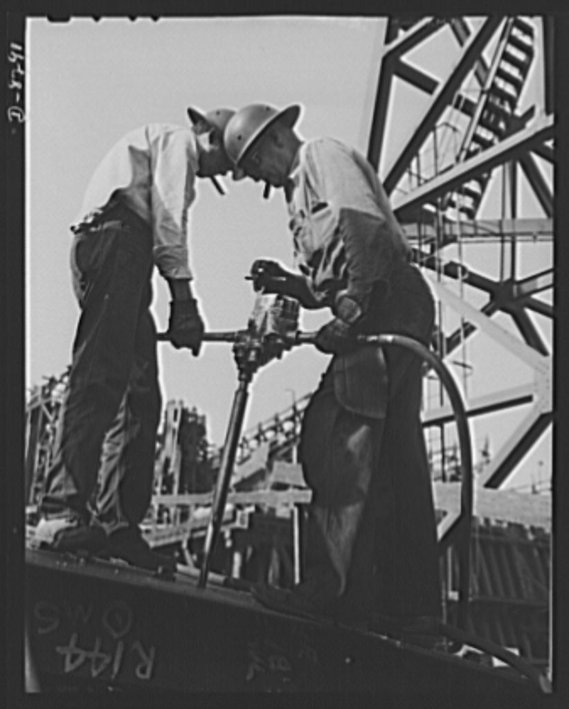 Manpower. Shipyard workers. Reaming holes in a deck plate for a new cargo boat under construction at the Wilmington, California, yard of the California Shipbuilding Corporation. The Booker T. Washington, recently launched at this yard, is one of the many freighters the company has built since Pearl Harbor