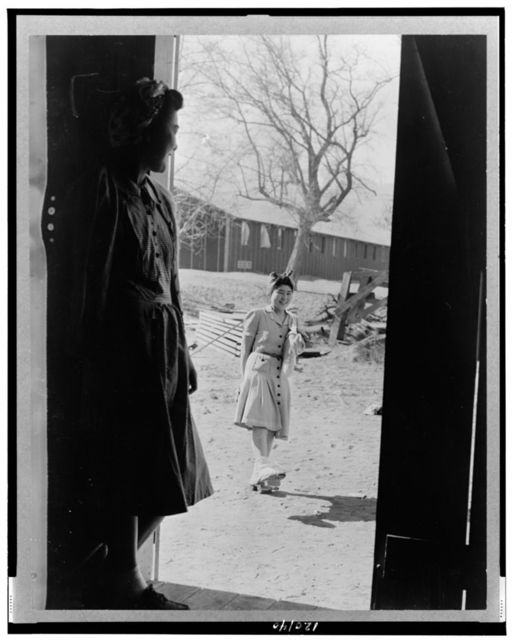 Manzanar, Calif. Apr. 1942--Yaeko Yamashita, in doorway, watching Fugiko Koba trying a new pair of geta, which are stilt-like sandals especially useful in dust--They are evacuees of Japanese descent living at the War relocation authority center / photo by Albers.