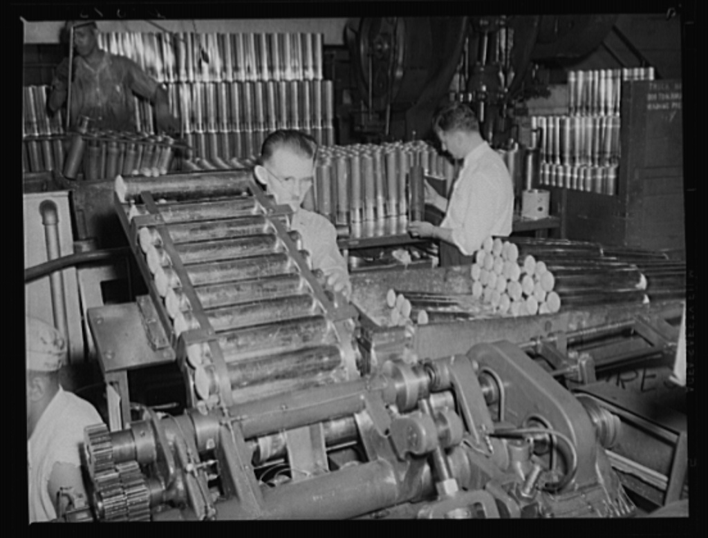 Mass production for the Army. 75 mm cartridge cases being trimmed by an accurate machine between draws. The production line is moving at top speed at a large eastern arsenal
