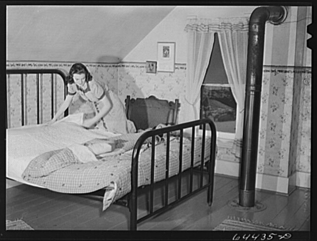 Meeker County, Minnesota. Elaine McCormick, one of the McRaith grandchildren, making the beds in the morning before the school bus comes