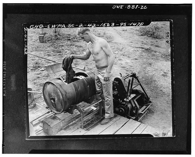 Members of the United States tank force in New Guinea constructed the ingenious washing machine from two old drums and a motor-driven wire-laying winch. Private First Class Wally Rathgeb of Wenatchee, Washington, is doing his weekly wash