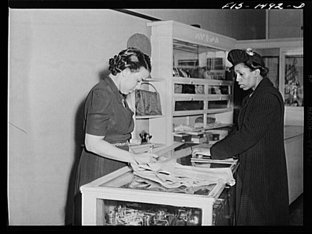 Miss Anita Francois, left, salesgirl in the Rosetta Frocks dress shop, selling a skirt to a customer. Chicago, Illinois