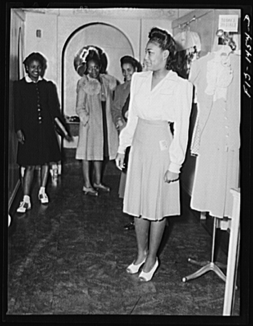 Miss Dorothea Owens trying on a new skirt in the Rosetta Frocks dress shop which is owned by Miss Cecilia Hall (Negro). Chicago, Illinois