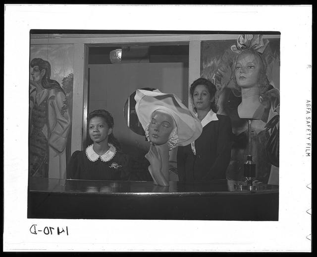 Miss Minnie Coleman (left), clerk, and Miss Selma Barbour (right), manager of the Cecilian Specialty Hat Shop, 454 East 47th Street, Chicago, Illinois