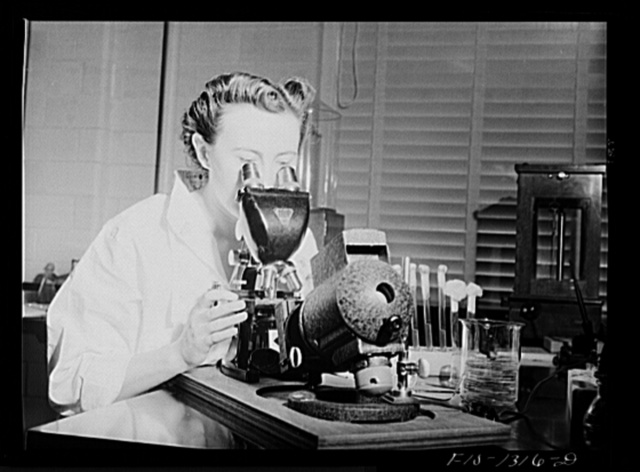 Miss Moore, assistant to Doctor Cox, at microscope. USPHS (United States Public Health Service)  Rocky Mountain Laboratory. Hamilton, Montana