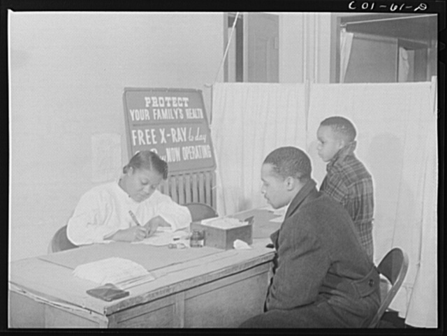 Miss Olive Smith interviewing applicants for x-rays at the x-ray clinic at the hospital of the Ida B. Wells Housing Project, Chicago, Illinois