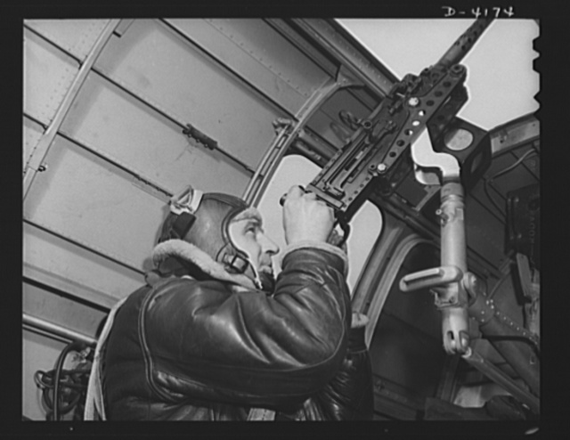 Mitchell Field. An American knight of the air mans the upper gun of one of our new bombers. He, his gun and his plane are typical of the personnel and equipment that have gained world respect for the American Air Force
