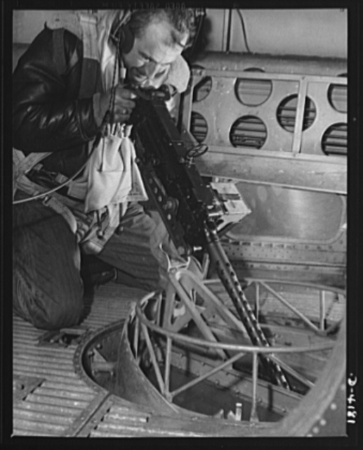 Mitchell Field. Bad news for the Axis when the rear-belly turret gun of an American bomber speaks its piece. The air crew officer at the gun is equipped for any emergency of flight or combat